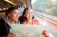 Chinese couple reading map on train