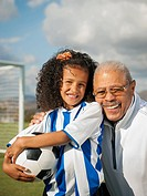 Man smiling with granddaughter on soccer field