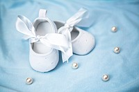 White baby booties on blue blanket