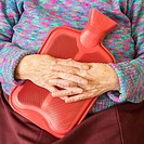 Elderly lady kkeping warm in winter with hot water bottle  England, United Kingdom