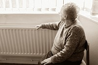 Ninety year old lady with hand on radiator looking out of window  England, United Kingdom