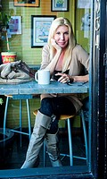 A 48 year old blond woman in casual clothing relaxing in a coffee shop seen through the window