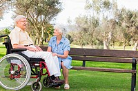 Woman talking to partner in wheelchair in the park