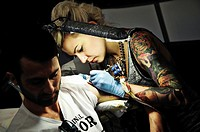 12 11 2011 Warsaw, Poland  Man drinks beer while woman tattooist works on his new tattoo during the tattoo, body painting and pierceing show - 'Body A...