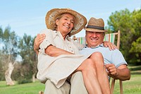 Woman sitting on lap of partner sitting in deck chair