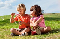 Little boy and girl blowing bubbles