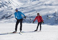 Germany, Man and woman skiing in snow