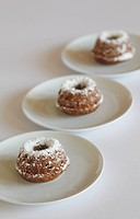 Miniature cakes with powdered sugar on plate