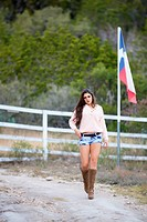 USA, Texas, Cowgirl walking on ranch
