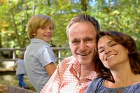 Germany, Bavaria, Family sitting on bench, smiling, portrait
