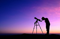 The silhouette of a teenage boy stargazing with a telescope at dusk