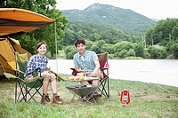 a couple sitting on camping chairs smiling at camera while having a camping meal