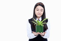 a female student wearing school uniform holding a plant pot