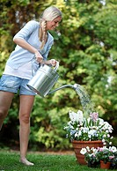 Smiling young woman in garden watering flowers