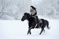 Young woman riding on horse in snow