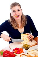 Woman eating olives and cutting emmenthal cheese