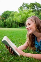 Young smiling woman lying in a parkland while holding a book