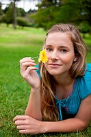 Young relaxed girl holding a yellow flower while lying in a park