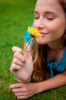 Young relaxed girl smelling a flower while lying on the grass