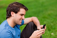 Young man sending a text with his cellphone while sitting on the grass