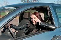 junge frau mit handy im auto