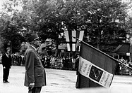 The French actor Adrien Cayla-Legrand attending the Liberation Day ceremony in the film The day of the jackal. The flag reminds the soldiers of the Fi...