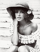 American actress Sydne Rome wearing a straw hat, sitting and posing. Rome, 1970s.