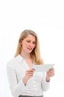 Junge Frau schaut interessiert auf einen Briefumschlag