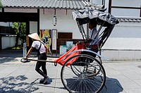 Man pulling a rickshaw in front of a temple, Kyoto, Japan, Asia