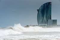 Big waves in stormy weather with W Barcelona Hotel as background, Barcelona, Catalonia, Spain