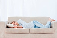 A woman is lying on a couch resting her head on a pillow