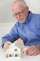 Caucasian businessman working on model of house