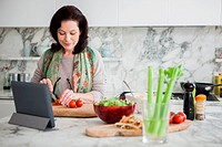 Woman cooking with tablet computer