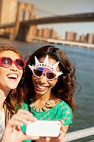 Women in novelty sunglasses taking picture by city cityscape