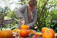 Teenage boy carving pumpkins outdoors