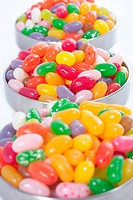 three bowls with colored sweet beans with short focus . Bright colored picture