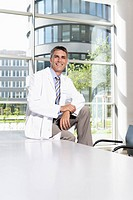 Doctor sitting on desk in meeting room