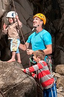 Man teaching children to rock climb