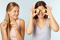 Teenage girls with cucumbers over eyes