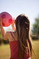 Girl carrying soccer ball in field