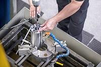 Worker drilling steel rod in factory