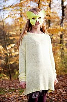 Girl wearing butterfly mask in park