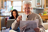 Hispanic man drinking coffee and reading newspaper