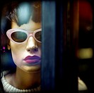 Female mannequin with retro glasses behind glass looking at the camera