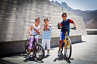 Three boys with bicycles posing for a photo in the Plaza de Espana in Adeje, Tenerife, designed by the Canarian architect Fernando Menis. It has been ...