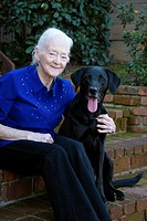 An old woman poses with her black lab best friend