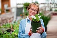 Senior woman holding flower pot