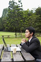 Young Asian businessman in a park with his laptop