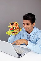 Young business man playing with a Chinese lion toy at work
