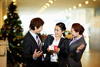 Businesswoman holding gift with colleagues beside her